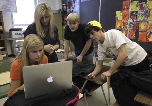 In this photo taken Friday, March 16, 2012 in Schofield, Wis., D.C. Everest Senior High prom committee adviser and english teacher Renee Buchholz, second left, looks on as, from left, juniors Khalia Kulppi, Zackry Wiese, and Brandon Dively consider their options in purchasing rubber bracelets to raise money for the high school in Henryville, Ind. that was destroyed after powerful storms ripped through southern Indiana on March 2. Henryville won a free concert by country music trio Lady Antebellum on Tuesday, March 20, following an online campaign that saw students in other states, including those at Everest, advocating on the school's behalf. (AP Photo/The Wausau Daily Herald, Dan Young) NO SALES