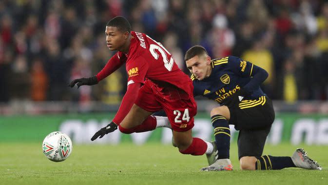 Pemain Liverpool, Rhian Brewster, terjatuh saat berebut bola dengan pemain Arsenal, Lucas Torreira, pada laga Piala Liga Inggris 2019 di Stadion Anfield, Rabu (30/10). Liverpool menang adu penalti atas Arsenal dengan skor 5-4. (AP/Jon Super)