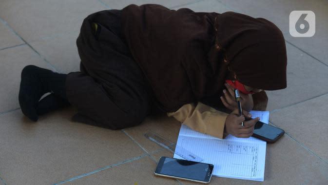 Siswa belajar di kolong rel kereta api Mangga Besar, Jakarta,Rabu (19/8/2020). Proses belajar siswa tersebut menggunakan modem paket internet wifi gratis yang disediakan untuk mengikuti pembelajaran jarak jauh. (merdeka.com/Imam Buhori)
