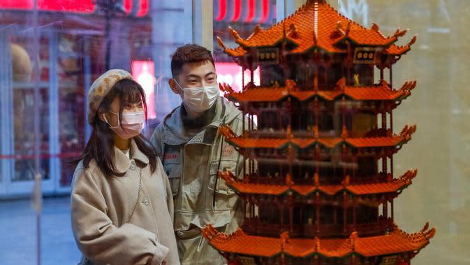 Orang-orang berhenti di salah satu toko di sebuah jalan kawasan perniagaan di Wuhan, Provinsi Hubei, China tengah, pada 30 Maret 2020. Jalan-jalan kawasan perniagaan di Wuhan kembali ramai seiring meredanya wabah COVID-19. (Xinhua/Shen Bohan)