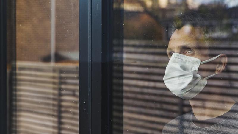 man looking through window wearing mask
