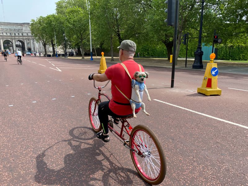 FILE PHOTO: A man takes advantage of London's empty streets to take his dog for a spin as the coronavirus lockdown continues