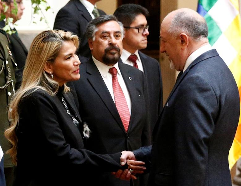 Bolivia's interim President Jeanine Anez shakes hand with Vladimir Sprichan, Russia's ambassador to Bolivia during a ceremony at the presidential palace in La Paz
