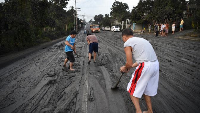 Warga membersihkan jalanan dari abu vulkanik setelah erupsi Gunung Taal di Tagaytay, Provinsi Cavite, Filipina, Senin (13/1/2020). Gunung yang terakhir meletus pada tahun 1977 tersebut melontarkan abu vulkanik mencapai 50.000 kaki (15.000 meter) ke atmosfer. (TED ALJIBE/AFP)