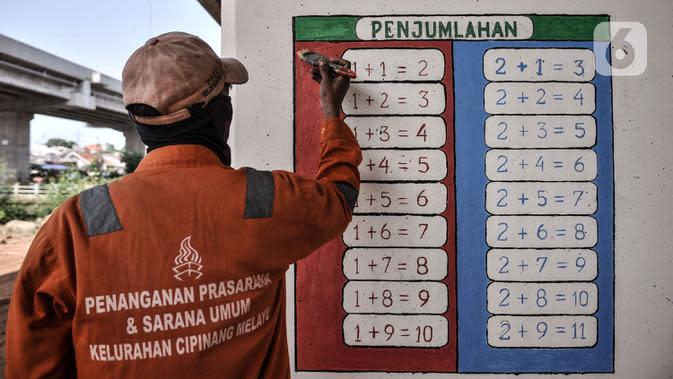 Petugas PPSU saat menyelesaikan mural edukasi untuk anak-anak di Taman Pilar Jati, Kolong Tol Becakayu, Jakarta, Selasa (8/9/2020). Taman ini dibangun untuk mengubah lahan kosong yang kerap dijadikan parkir liar menjadi RTH yang dapat bermanfaat bagi warga. (merdeka.com/Iqbal S. Nugroho)