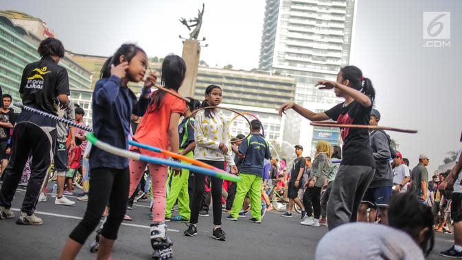 Anak-anak bermain permainan tradisional hula hoop ditemani sejumlah mahasiswa dari Penggerak Olahraga saat car free day (CFD) di kawasan Bundaran HI, Jakarta, Minggu (14/7/2019). Kegiatan yang rutin digelar ini bertujuan mengajak masyarakat DKI Jakarta aktif berolahraga. (Liputan6.com/Faizal Fanani)