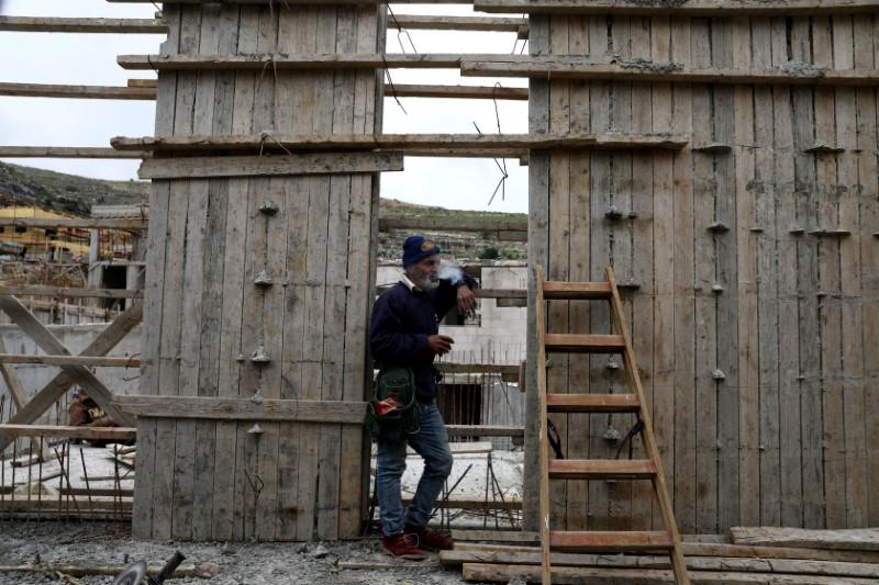 A Palestinian labourer smokes a cigarette at a construction site in the Israeli settlement of Ramat Givat Zeev in the Israeli-occupied West Bank