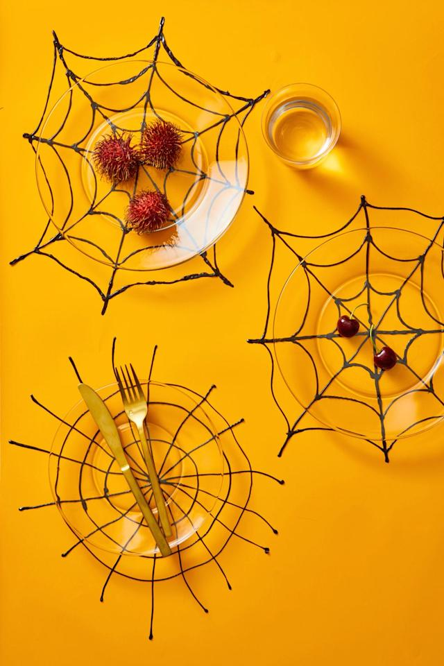 """<p>You can make your own fun placemats using nothing but puff paint and parchment paper. Just make a web shape onto the paper with the puff paint, then let it set overnight so you can peel the paper off the back. Place underneath a clear plate to show off the design!</p><p><a class=""""body-btn-link"""" href=""""https://www.amazon.com/Fabric-Paint-Set-Brushes-Stencils/dp/B07F1KCYH7/?tag=syn-yahoo-20&ascsubtag=%5Bartid%7C10055.g.1566%5Bsrc%7Cyahoo-us"""" target=""""_blank"""">SHOP PUFF PAINT</a><br><strong></strong></p><p><strong>RELATED:</strong> <a href=""""https://www.goodhousekeeping.com/holidays/halloween-ideas/g421/halloween-decorating-ideas/"""" target=""""_blank"""">60+ Easy Halloween Decor Ideas to Give Your Home a Spooky Makeover</a><br></p>"""