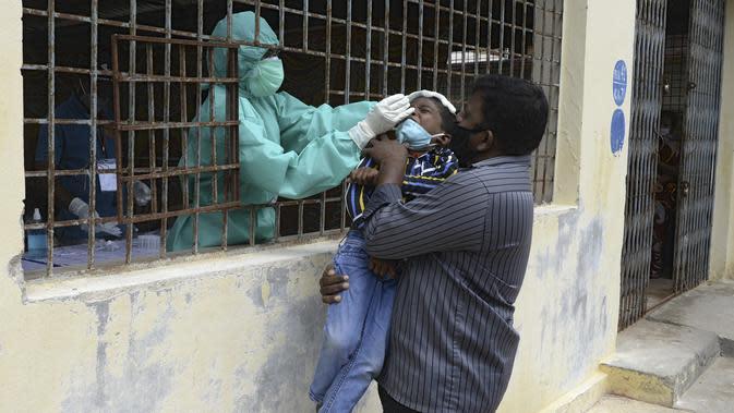 Seorang pria menggendong putranya saat petugas kesehatan mengumpulkan sampel usap untuk menguji virus corona Covid-19 di daerah kumuh di Hyderabad (23/9/2020). Korban meninggal karena Covid-19 di India mencapai 90.000 lebih. (AFP/Noah Seelam)