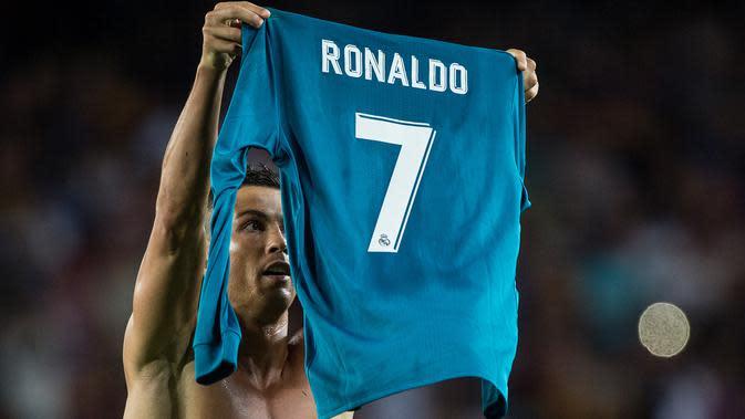 Pemain Real Madrid, Cristiano Ronaldo mengangkat jerseynya tinggi-tinggi di hadapan suporter Camp Nou pada leg pertama Piala Super Spanyol, Senin (14/8). Aksi selebrasi Ronaldo usai mencetak gol ke gawang Barcelona itu menjadi sorotan. (STRINGER/AFP)