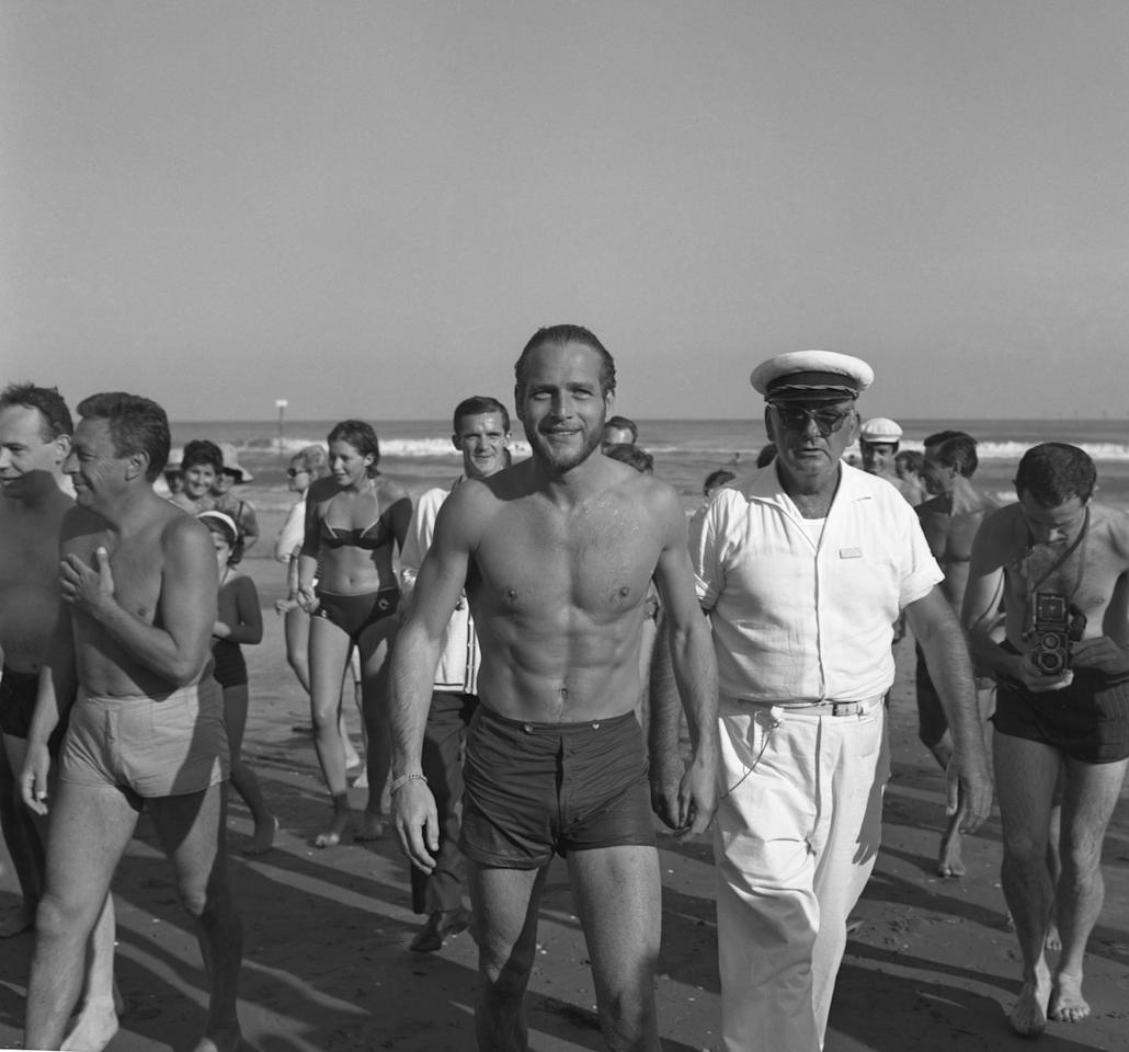 <p>Paul Newman smiles at the camera as he walks along the seashore in 1963.</p>