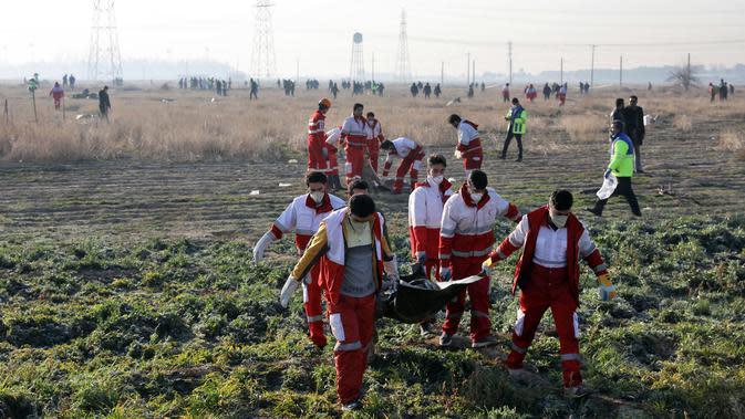 Tim penyelamat membawa jasad korban jatuhnya pesawat Boeing 737-800 di Shahedshahr, Iran, Rabu (8/1/2020). Korban tewas terdiri dari 82 warga Iran, 63 warga Kanada, 11 warga Ukraina, 10 warga Swedia, 4 warga Afghanistan, 3 warga Jerman, dan 3 warga Britania Raya. (AP Photo/Ebrahim Noroozi)