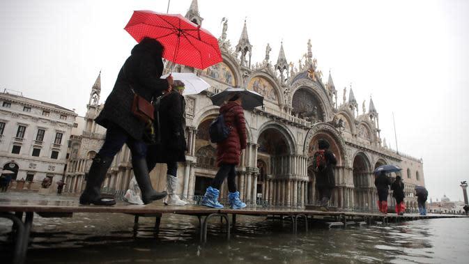 Sejumlah warga berjalan melewati papan saat gelombang pasang membuat banjir depan Basilika Santo Markus, Venesia, Italia, Selasa (12/11/2019). Venesia dilanda banjir akibat gelombang pasang setinggi 127 cm. (AP Photo/Luca Bruno)