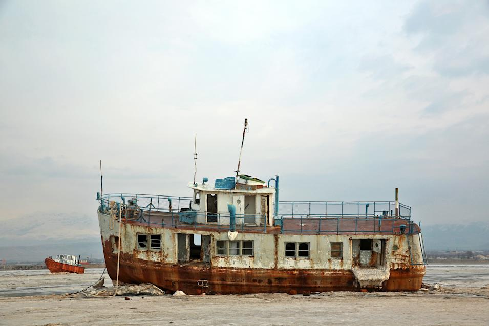 In this Sunday, Feb. 16, 2014 photo, abandoned vessels are stuck in the solidified salts at Lake Oroumieh, northwestern Iran. Oroumieh, one of the biggest saltwater lakes on Earth, has shrunk more than 80 percent to 1,000 square kilometers (nearly 400 square miles) in the past decade. Experts fear the lake -- famous in years past as a tourist spot and a favorite stopping point for migrating flamingos, pelicans and gulls -- could disappear within two years if nothing is done. (AP Photo/Ebrahim Noroozi)