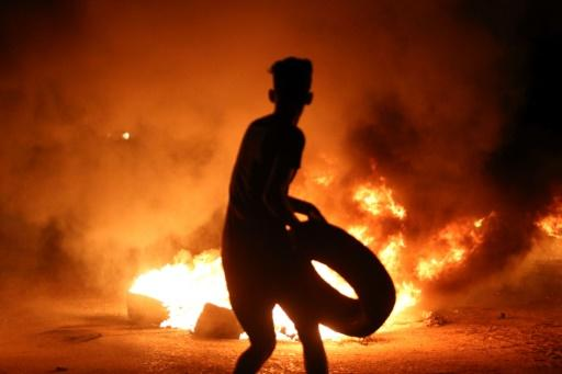 A demonstrator burns tyres during protests against unemployment and high cost of living in the southern Iraqi city of Basra during the night of July 12, 2018