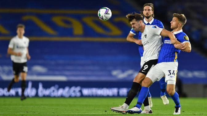 Bek Brighton, Joel Veltman, berebut bola dengan striker Portsmouth, John Marquis, pada laga Piala Inggris di Falmer Stadium, Jumat (18/9/2020) dini hari WIB. Brighton menang 4-0 atas Portsmouth. (AFP/Glyn Kirk/pool)