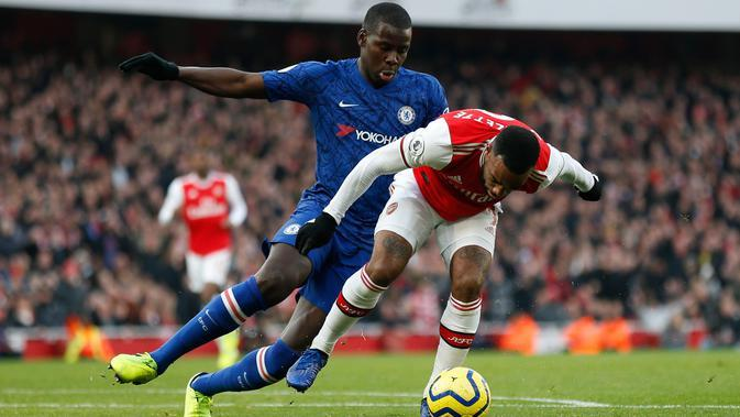 Bek Chelsea, Kurt Zouma berebut bola dengan striker Arsenal, Alexandre Lacazette pada lanjutan Liga Inggris di Emirates Stadium, Minggu (29/12/2019). The Blues –julukan Chelsea, mampu menutup laga dengan skor akhir 2-1 di kandang Arsenal. (Adrian DENNIS / AFP)