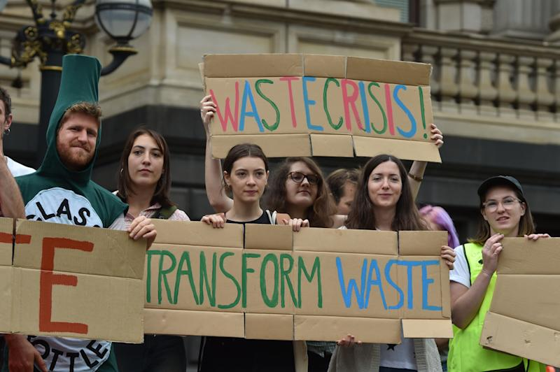 Demonstrators hold signs outside the Parliament of Victoria about the recycling crisis.