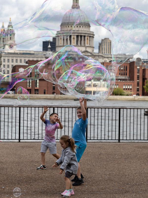 Anak-anak bermain gelembung tiup di tepi Sungai Thames dengan latar pemandangan Katedral St. Paul di London, 1 Agustus 2020. Pemerintah Inggris pada Jumat (31/7) mengumumkan penundaan pelonggaran beberapa langkah pembatasan menyusul jumlah infeksi virus corona yang meningkat. (Xinhua/Han Yan)