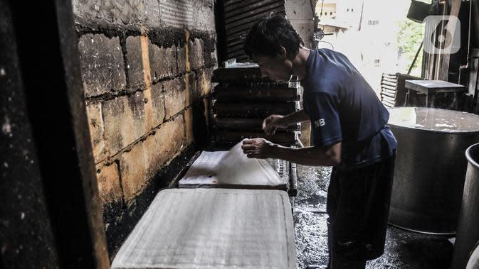 Pekerja menyelesaikan pembuatan tahu di industri rumahan kawasan Mampang, Jakarta, Minggu (30/8/2020). Menurunnya produksi disebabkan pelanggan, terutama pengusaha warung makan yang terpaksa tutup akibat diterapkannya PSBB sehingga berpengaruh pada omzet penjualan. (merdeka.com/Iqbal S. Nugroho)