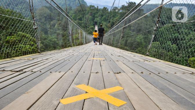 Tanda jaga jarak terpasang di lantai Jembatan Gantung Situ Gunung, Sukabumi, Jawa Barat, Minggu (20/9/2020). Dari rata-rata 2.500 pengunjung tiap harinya kini hanya di bawah 1.000 pelancong per hari akibat merebaknya pandemi Covid-19 serta adanya penerapan PSBB. (merdeka.com/Iqbal S. Nugroho)