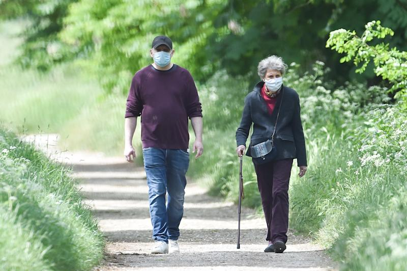 PARIS, FRANCE - MAY 04: People wearing protective masks walks in the Bois de Vincennes as the lockout continues due to the coronavirus epidemic (COVID 19) on May 04, 2020 in Paris, France. The coronavirus pandemic (COVID-19) has spread to many countries around the world, killing more than 249,000 and infecting more than 3.5 million people. (Photo by Stephane Cardinale - Corbis/Corbis via Getty Images)