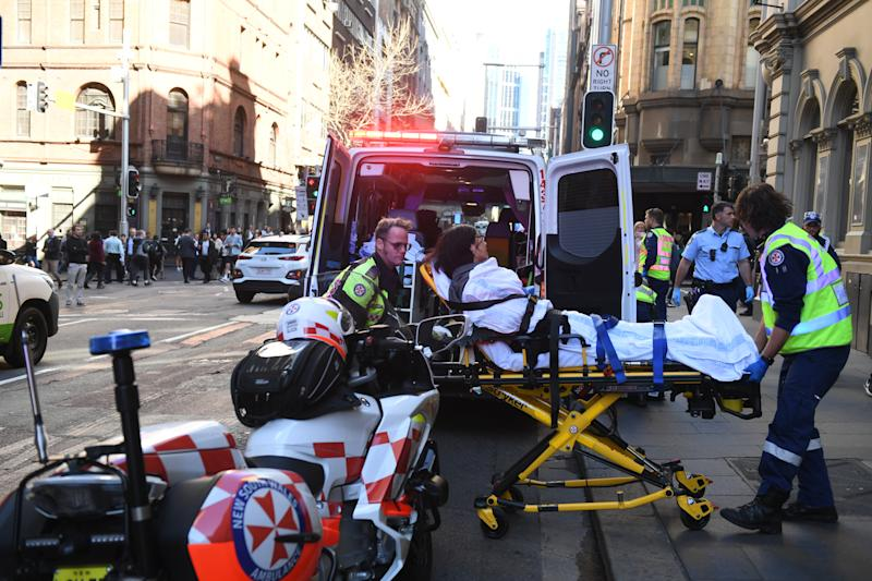 Paramedics load a woman into an ambulance after a man is stabbed in the Sydney CBD.