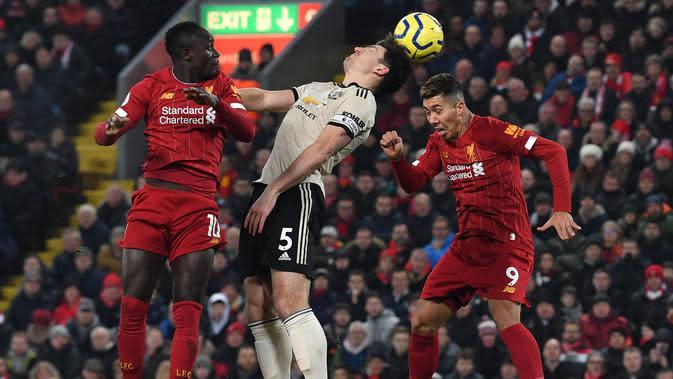 Gelandang Liverpool, Roberto Firmino, duel udara dengan bek Manchester United, harry Maguire, pada laga Premier League di Stadion Anfield, Liverpool, Minggu (19/1). Liverpool menang 2-0 atas MU. (AFP/Paul Ellis)