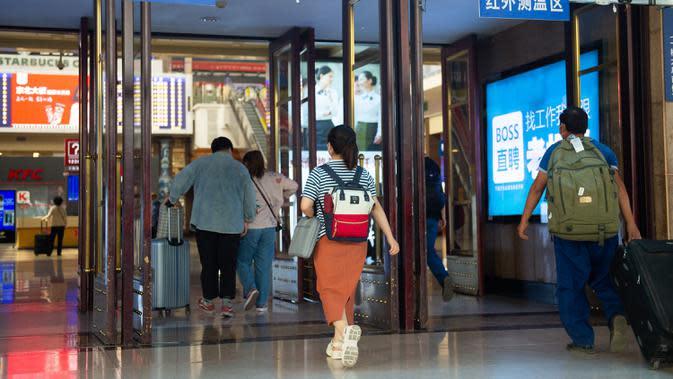 Para penumpang berjalan melewati area pemantauan suhu tubuh di aula Stasiun Kereta Api Beijing di Beijing, ibu kota China (18/6/2020). (Xinhua/Chen Zhonghao)