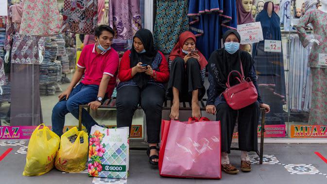 Keluarga yang mengenakan masker untuk mengantisipasi penyebaran virus corona COVID-19 duduk di luar toko setelah berbelanja menjelang Idul Fitri di Kuala Lumpur, Malaysia, Kamis (21/5/2020). Hari Raya Idul Fitri menandai berakhirnya bulan suci Ramadan. (Mohd RASFAN/AFP)