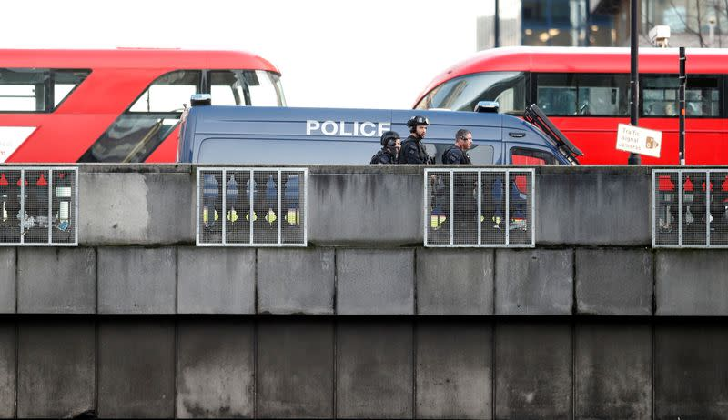 Police officers and emergency staff work at the site of an incident at London Bridge