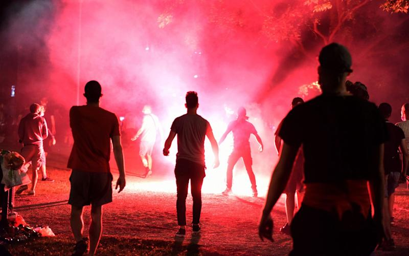 Protesters light flares as they attend a rally against the government's lockdown measures in front of the parliament in Belgrade, Serbia - Reuters