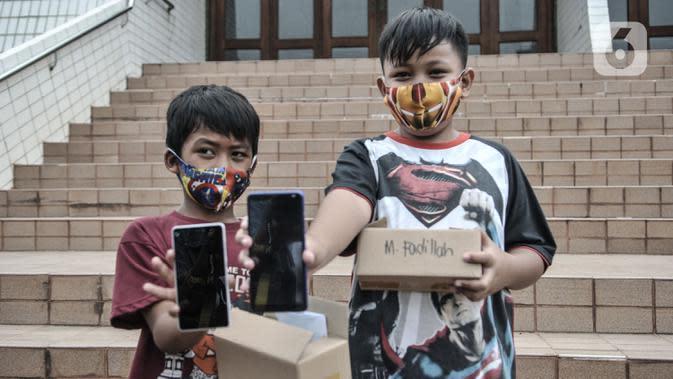 Anak-anak menunjukkan ponsel saat acara #PonselPintarUntukPelajar, Jakarta, Minggu (9/8/2020). #PonselPintarUntukPelajar merupakan serangkaian kegiatan donasi yang dilakukan #WartawanLintasMedia bertujuan membantu masyarakat kurang mampu di masa pandemi Covid-19. (merdeka.com/Iqbal S. Nugroho)