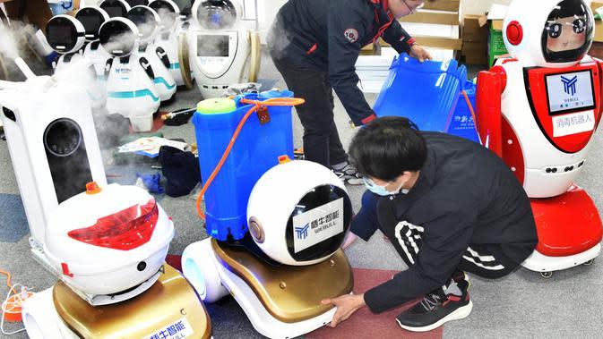 Para teknisi menyetel robot desinfeksi di sebuah perusahaan teknologi di Qingdao, Provinsi Shandong, China, 11 Februari 2020. Beberapa robot desinfeksi ini telah digunakan di ruang isolasi sejumlah rumah sakit di China. (Xinhua/Li Ziheng)