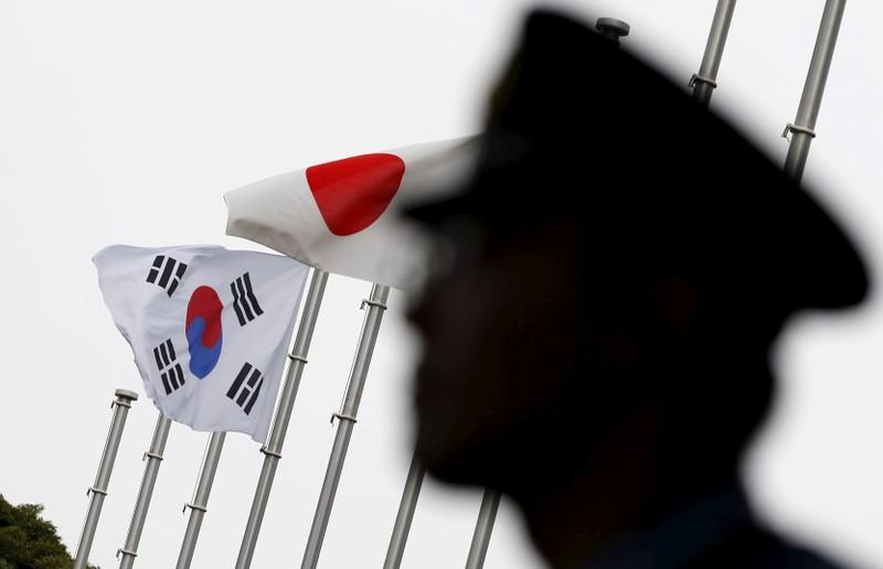 FILE PHOTO: Police officer stands guard near Japan and South Korea national flags at a hotel in Tokyo