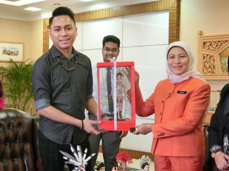 Wesley, at left, presents Tourism Minister Nancy Shukri with a Borneo Barbie doll. Photo: Nancy Shukri/Facebook