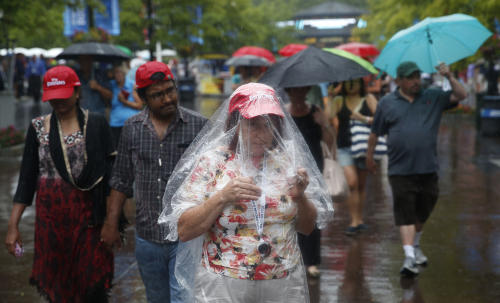 Tennis fans exit the Billie Jean King National Tennis Center during a rain delay at the 2014 U.S. Open tennis tournament, Sunday, Aug. 31, 2014, in New York. (AP Photo/Seth Wenig)