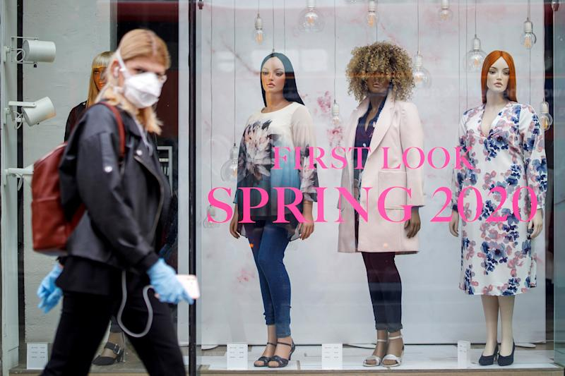 """A woman wearing PPE (personal protective equipment), of a face mask as a precautionary measure against COVID-19, walks past an Evans clothing store, closed-down due to coronavirus, on Oxford Street in central London on April 27, 2020. - Prime Minister Boris Johnson on Monday made his first public appearance since being hospitalised with coronavirus three weeks ago, saying Britain was beginning to """"turn the tide"""" on the outbreak but rejecting calls to ease a nationwide lockdown. (Photo by Tolga AKMEN / AFP) (Photo by TOLGA AKMEN/AFP via Getty Images)"""