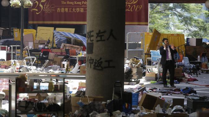 Seorang pria dikelilingi oleh sampah setelah protes besar-besaran di kampus Universitas Politeknik di Hong Kong (22/11/2019). Enam pemrotes bertopeng dari universitas menyerah pada Jumat pagi, sehingga jumlahnya sekitar 30 yang telah keluar. (AP Photo/Achmad Ibrahim)