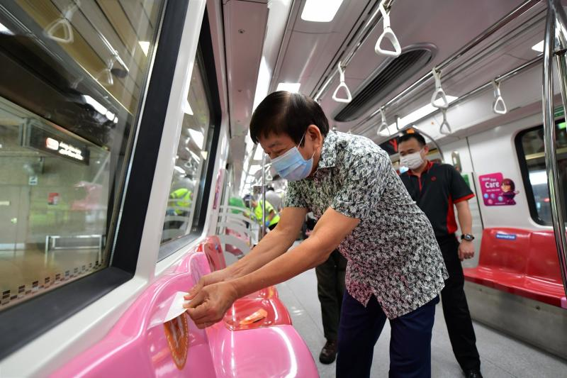 Transport Minister Khaw Boon Wan removing a safe distancing sticker from the seat of an MRT train. (PHOTO: Facebook / Khaw Boon Wan)