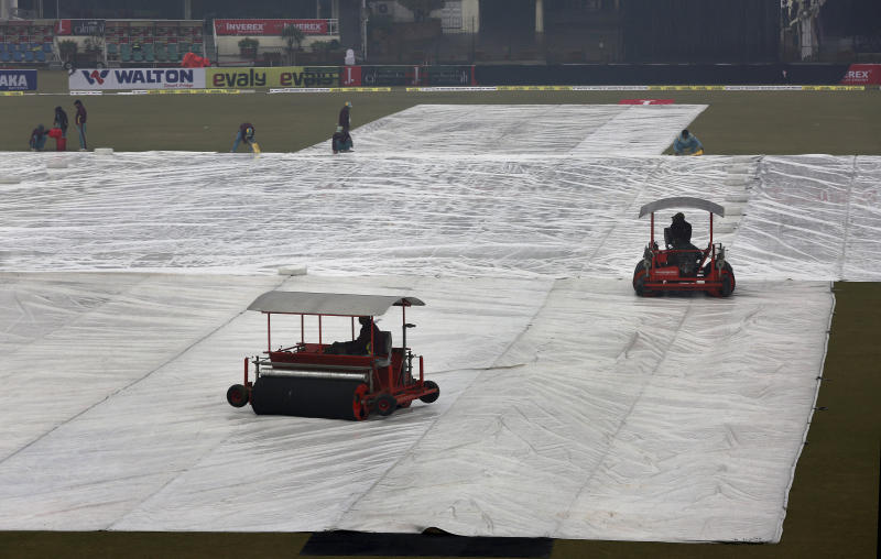Ground staff work to dry the pitch and field following a light rain at Gaddafi stadium, in Lahore, Pakistan, Monday, Jan. 27, 2020. Pakistan and Bangladesh are scheduled to play the last T20 which is delayed due to rain in Lahore. (AP Photo/K.M. Chaudary)