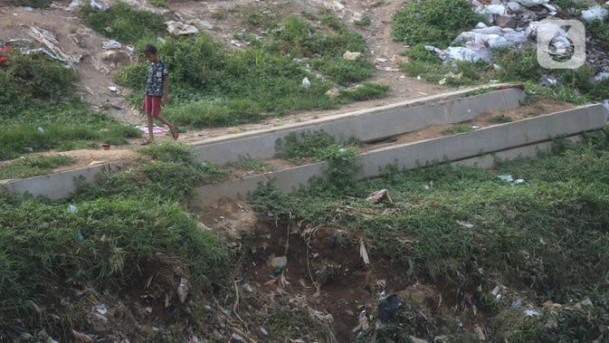 Seorang anak bermain dekat tiang pancang untuk pembangunan dinding turap di Kali Ciliwung, Rawajati, Kalibata, Jakarta, Jumat (25/9/2020). Tumpukan tiang pancang untuk pembangunan dinding turap sebagai bagian dari proyek normalisasi Kali Ciliwung itu tampak terbengkalai. (merdeka.com/Imam Buhori)