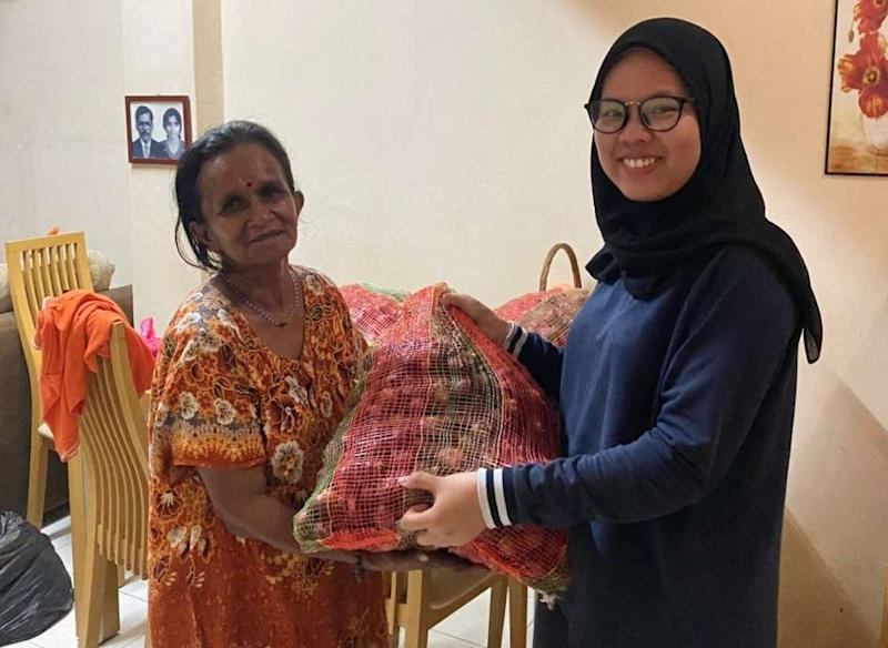 Roob Ganesan's friend, Adibah Atiqah, giving Mahamachumy a sack of onions to be peeled August 4, 2020. — Picture courtesy of Roob Ganesan