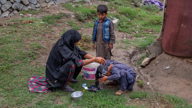 Khalida, perempuan pengembara Kashmir Bakarwal mencuci rambut putrinya di luar kamp sementara di pinggiran Srinagar, India, 31 Agustus 2020. Suku Bakarwals adalah kaum penggembala nomaden di Jammu Kashmir, yang berpindah-pindah mencari padang rumput yang baik untuk ternak mereka. (AP Photo/Dar Yasin