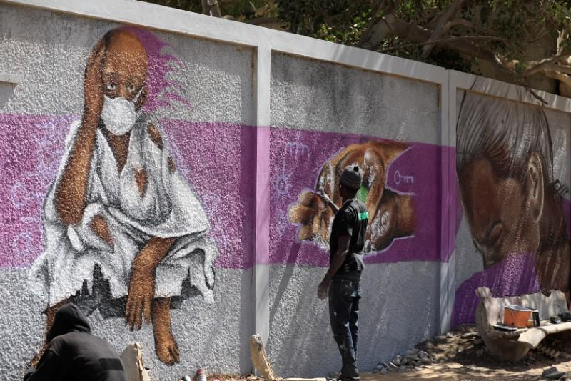 A graffiti artist from RBS crew works on his mural to encourage people to protect themselves amid the outbreak of the coronavirus disease (COVID-19), in Dakar