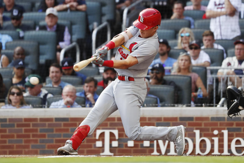 FILE - In this Oct. 9, 2019, file photo, advertising is seen in the background as St. Louis Cardinals' Tommy Edman hits a double during the first inning of Game 5 of their National League Division Series baseball game against the Atlanta Braves, in Atlanta. While the coronavirus pandemic circles the world, sports business executives are having conversations about advertising and marketing contracts with no games on the horizon. (AP Photo/John Bazemore, File)