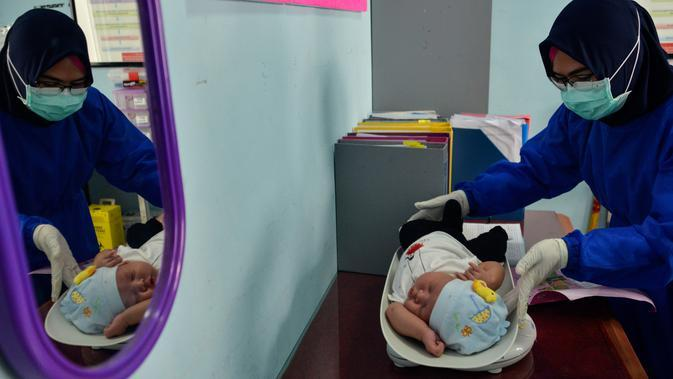 Petugas kesehatan menimbang berat badan bayi sebelum melakukan imunisasi di sebuah Pukesmas di Banda Aceh, Aceh, Senin (15/6/2020). Memasuki tatanan normal baru, pelayanan imunisasi anak kembali dibuka setelah sebelumnya sempat terhenti akibat pandemi COVID-19. (CHAIDEER MAHYUDDIN/AFP)