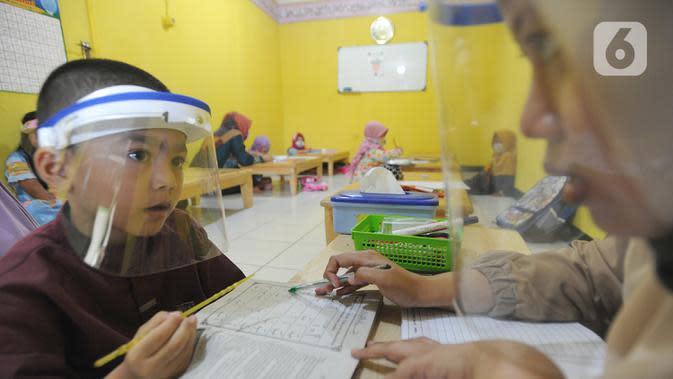 Murid menggunakan face shield belajar iqro di Taman Pendidikan Al-Qur'an (TPA) Al-Muthmainnah Cinere, Depok, Rabu (1/7/2020). Proses belajar mengajar dilakukan dengan protokol kesehatan dimana murid diwajibkan menggunakan masker atau face shield. (merdeka.com/Arie Basuki)