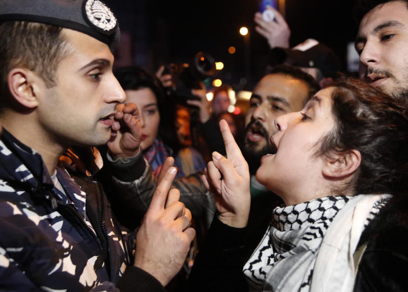 An anti-government protester, right, argues with a police officer, as protesters blocking a main road during ongoing protests against the ruling elite of corruption and financial crisis, in Beirut, Lebanon, Monday, Jan. 13, 2020. Lebanon is facing its worst economic crisis in decades, while protests against corruption and mismanagement have gripped the country since October. (AP Photo/Hussein Malla)