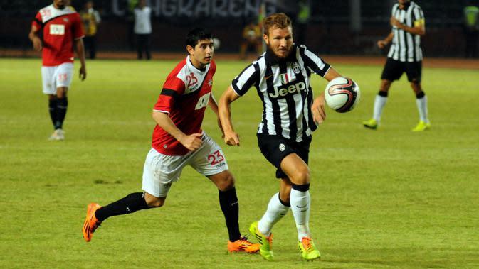 Marco Motta (Juventus - kanan) berebut bola dengan Esteban Vizcara (ISL All Stars) saat berlaga di Stadion GBK Jakarta, (6/8/2014). (Liputan6.com/Helmi Fithriansyah)